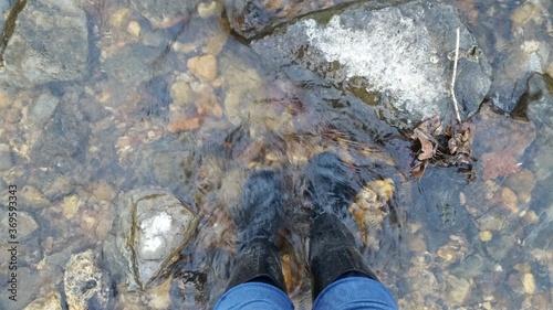 Tela standing in a creek wearing rain boots