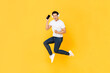 Happy young Asian man wearing headphone listening to music from mobile phone and jumping isolated on yellow background