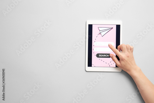 Obraz Hand with tablet computer on light background. Concept of online booking - fototapety do salonu