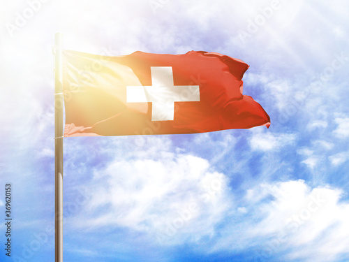 National flag of Switzerland on a flagpole in front of blue sky Fototapeta