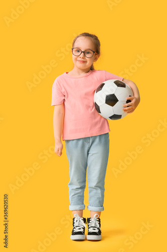 Fotografija Cute little girl with soccer ball on color background
