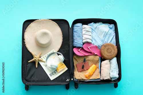 Obraz Packed suitcase with beach accessories on color background. Travel concept - fototapety do salonu