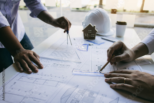Obraz Team architect or engineering people discussion working on table together at a construction site. - fototapety do salonu