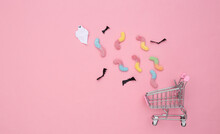 Supermarket Trolley With Handmade Bats And Ghost, Gummy Worms On Pink Pastel Background. Halloween Concept. Top View