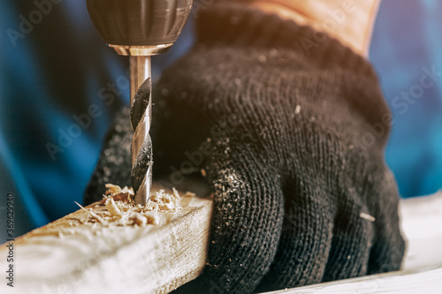 Obraz Close-up of a male construction worker in a black dirty construction overall closes a screw with a black modern screwdriver in a wooden block in the workshop - fototapety do salonu