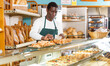Smiling African American baker working behind counter in small bakehouse, packing fresh pastry in paper bag