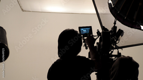 Silhouette of photographer checking for movie camera. Wallpaper Mural