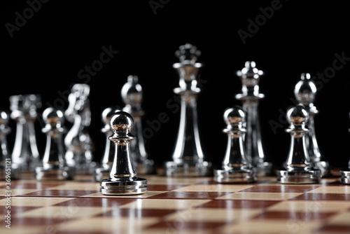 Fototapeta Steel chess figures standing on wooden chessboard