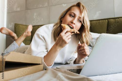 Fototapeta Woman eating pizza and using laptop computer obraz