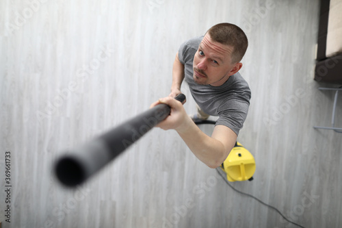 Photo A man collects dust from the ceiling with a vacuum cleaner