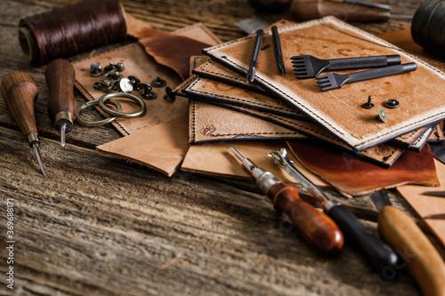 Slika na platnu Leather craft tools on old wood table. Leather craft workshop.