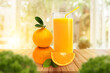 Fresh glass of orange juice, stack of Orange with leaves on wooden on warm light. Nature drinks.