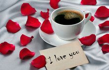 Romantic Coffee. Note I Love You, Cup Of Coffee And Red Rose Petals On A Slk Background. Coffee In A White Cup And Rose Petals.