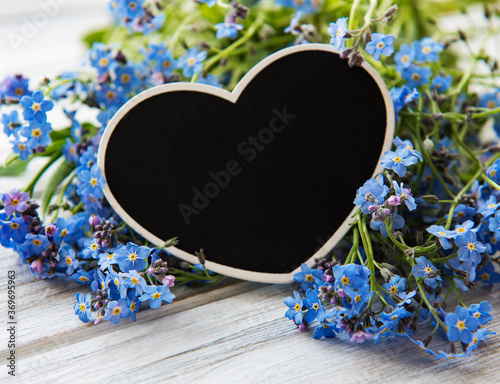 Forget-me-not flowers and black heart shaped board on white wooden background Wall mural