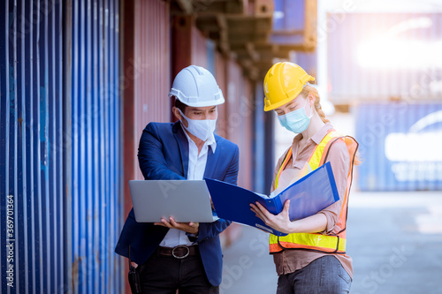 Obraz A Manager and dock worker under discussion about dock container shipping warehouse document, they wearing safety uniform hard hat and hold radio communication wearing face mask to protect virus. - fototapety do salonu