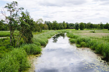 Narrow River In A Rural Area, Reflection Of The Sky And Clouds In The Water, Grassy Fields On Both Sides