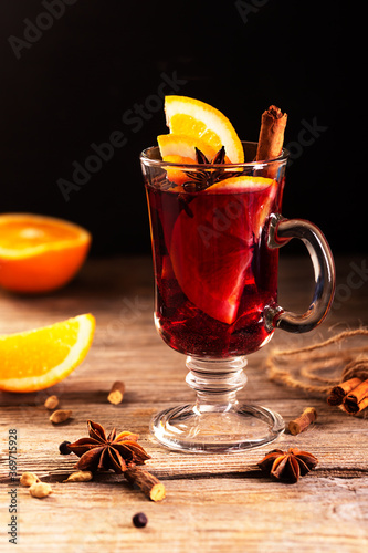 Leinwand Poster Mulled wine with slice of orange and spices on a wooden background