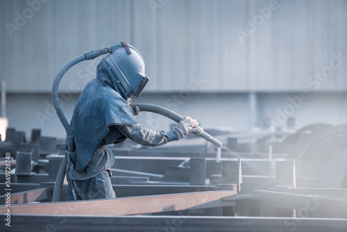 Fotografia Sand blasting process, Industial worker using sand blasting process preparation cleaning surface on steel before painting in factory workshop