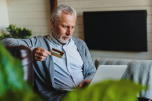 Senior Man Sitting On Sofa With Laptop And Using Credit Card