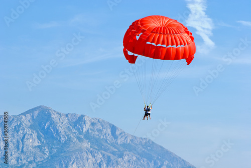Fotografia Tandem, two persons flying on a red parachute on sky background