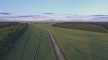 The Car Drives Through A Gravel Road Towards A Wind Turbine In Agricultural Fields. Aerial Tracking Vehicle