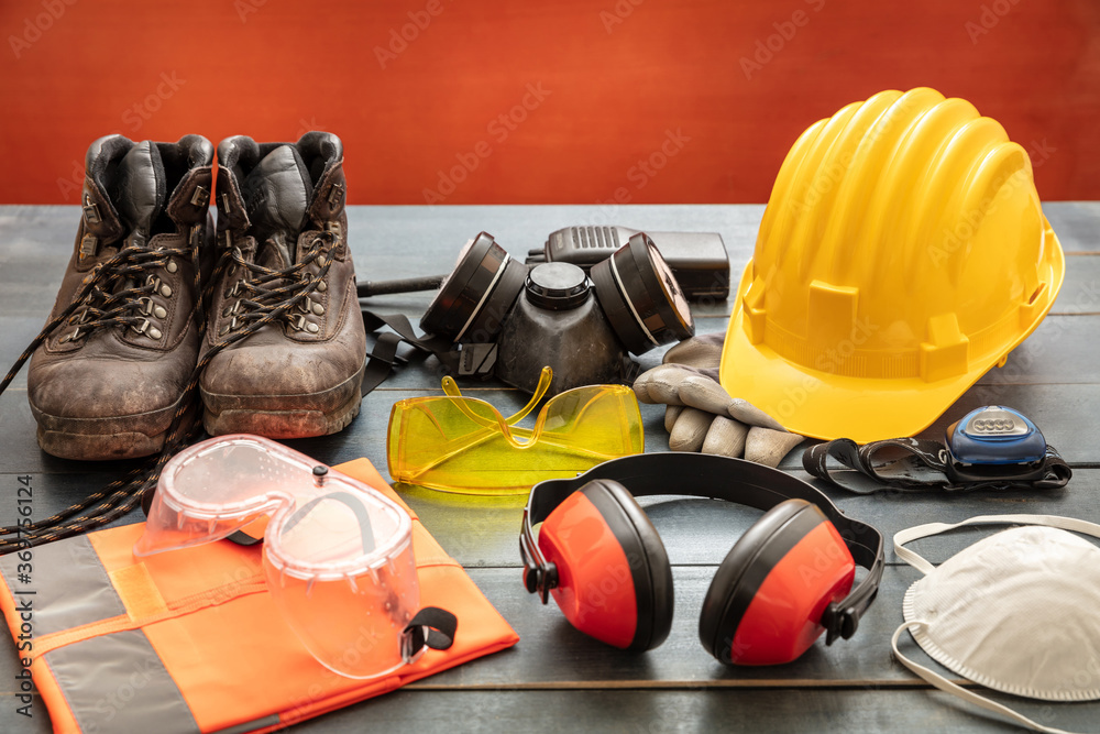 Fototapeta Work safety protection equipment. Industrial protective gear on wooden table, red color background.