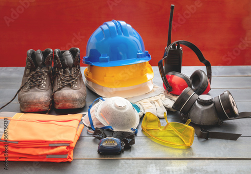 Work safety protection equipment. Industrial protective gear on wooden table, red color background.