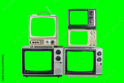 Fototapeta Five vintage televisions on old wood table with green screens and backgrounds. obraz