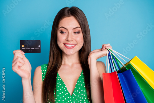 Close up photo of positive cheerful girl hold look credit bank card pay many bags wear style stylish trendy singlet isolated over blue color background