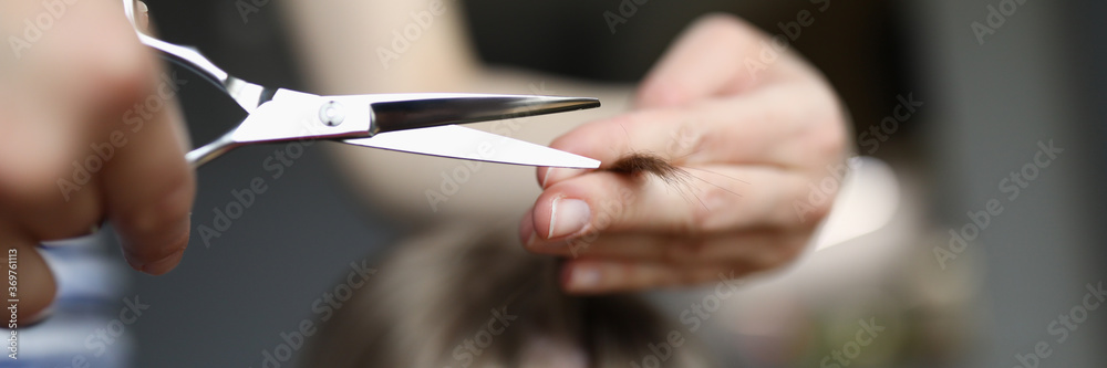 Fototapeta Mom cuts baby hair with scissors at home, hairstyle. Woman does hairstyle for child at home during quarantine. Hairdresser works on visit to clients house. Hair trendy stylist training