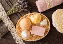 Top View Still Life Of Various Bath Products In Wood Wicker Basket. Bath Bomb, Bar Of Soap, Natural Sea Sponge With Mother Pear Sea Shells. Flat Lay View With Dry Lavender Bouquet And Rolled Towel.