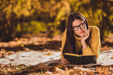 Photo Of Positive Girl Rest Relax In Autumn Forest Park Lawn Lying Checkered Plaid Blanket Read Interesting Book Wear Yellow Color Pullover