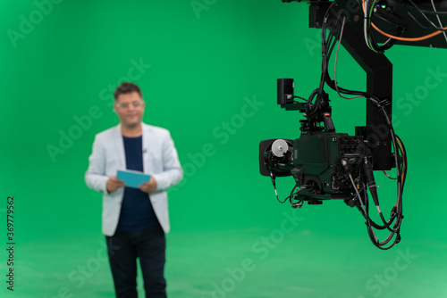 Broadcast television studio camera in greenscreen studio room with announcer on the ceiling.