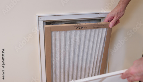 Replacing dirty central air conditioning  air filter Wallpaper Mural