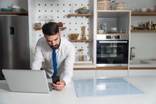 Young Bearded Business Man In Shirt With Neck Tie Standing In The Kitchen Holding Phone And Reading The Statistic On The Laptop Waiting For The Breakfast Before He Go To The Job In The Company