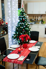 A Cozy Room With Table Setting For The New Year Against The Background Of A Festively Decorated Christmas Tree With Garlands And A White Kitchen.