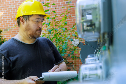 Vászonkép Closeup of electrical engineer in yellow helmet technician writing on clipboard