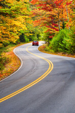 A Red Car Driving Through Winding Road With Beautiful Autumn Foliage Trees In New England