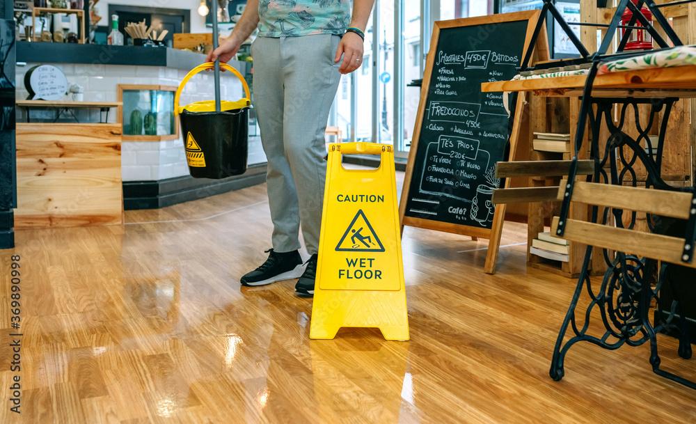 Fototapeta Worker placing wet floor sign after mopping the floor