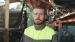 A young bearded auto mechanic wearing overalls stands in front of racks with spare parts. Close-up. Slow motion. The camera moves from left to right