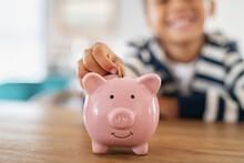 Smiling Child Saving Money In Piggybank