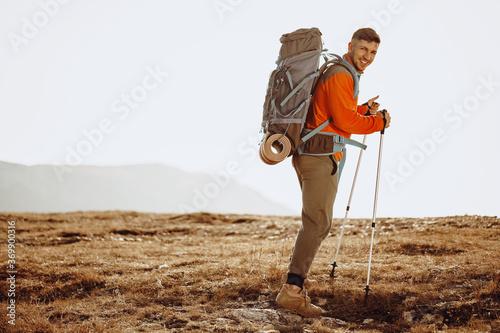 Obraz Man traveler with trekking sticks going up the mountain - fototapety do salonu