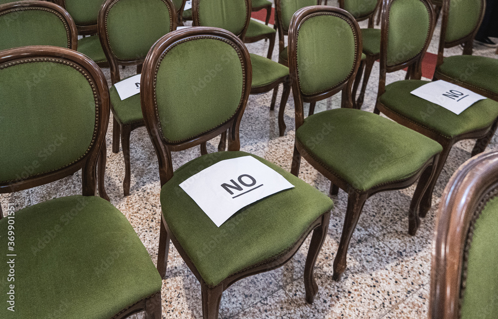 Fototapeta Alternately assigned seats in a conference or ceremony during the coronavirus pandemic due to social distancing provisions. Paper sheets saying no on top.