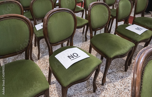 Obraz Alternately assigned seats in a conference or ceremony during the coronavirus pandemic due to social distancing provisions. Paper sheets saying no on top. - fototapety do salonu