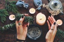 Wiccan Witch Holding Cedar Cleansing Stick To Cleanse The Energy At Her Altar. Female Woman Holding Evergreen Smoke Cleansing Stick In Her Hands. Candles Burning On Dark Wooden Surface Background