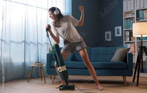 Fototapeta Woman cleaning up her house and singing