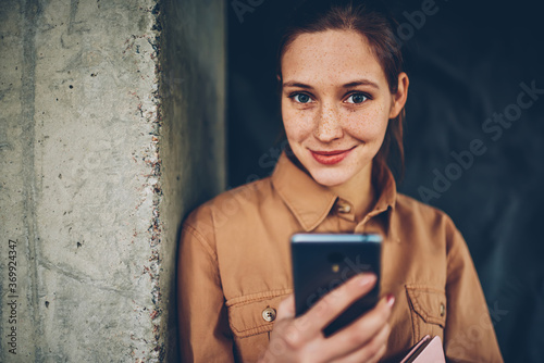Valokuvatapetti Half length portrait of attractive young woman holding smartphone in hands and updating profile in networks via 4G internet connection while looking at camera