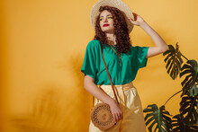 Summer Fashion Concept: Woman Wearing Trendy Green T-shirt, Yellow Bermudas Shorts, Straw Hat, With Round Shoulder Wicker Bag, Posing On Yellow Background. Copy, Empty Space For Text