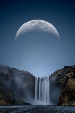 A Huge Moon Over Skogafoss Waterfall In Iceland