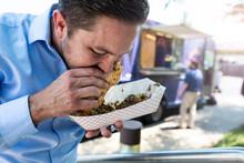 Food Truck: Man Eating Delicious Steak Sub Sandwich